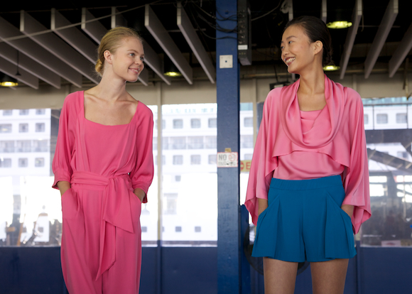 Models smile at each other at Catherine Malandrino Spring 2014 looks in pink and blue at New York Fashion Week